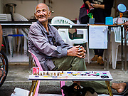 22 DECEMBER 2018 - CHANTABURI, THAILAND: A Thai man selling gems and Buddhist amulets talks to his friends in the gem market in Chantaburi. The gem market in Chantaburi, a provincial town in eastern Thailand, is open on weekends. Chantaburi used to be an active gem mining area in Thailand, but the mines are played out now. Now buyers and sellers come from around the world to Chantaburi for the weekend market. Many of the stones come from Myanmar, others come from mines in Afghanistan and Africa.     PHOTO BY JACK KURTZ