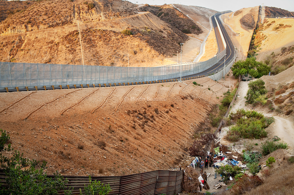 At the foot of the wall, literally, waiting for the right moment to pass. Dawn, dusk or foggy days are the best times for these men to try their luck. Most are deported repeatedly. Without Mexican identity papers (lost or confiscated by U.S. authorities during arrests), they are also illegal in their own country, and face jail if they are caught by local authorities. //// Tijuana, Mexique. Au pied du mur, littéralement, on attend le bon moment pour passer. Ces hommes ont pour la plupart vécu de nombreuses années aux Etats-Unis, avant d'être arrêtés et expulsés. Sans papiers, ils sont aussi clandestins dans leur propre pays : rares sont ceux qui ont une pièce d'identité mexicaine.