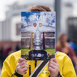 © Licensed to London News Pictures. 30/05/2015. London, UK. A boy holds up the match programme, as fans gather at Wembley Stadium for the FA Cup Final 2015, between Arsenal and Aston Villa. Photo credit : Stephen Chung/LNP