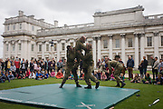 As families queue in the grounds of the Naval College, Greenwich, member of Royal Marines Commandos demonstration team show off their unarmed combat techniques. During a public open-day in Greenwich, when the Royal Navy's aircraft carrier HMS Illustrious docked on the river Thames, allowing the tax-paying public to tour its decks before its decommisioning. Navy personnel helped with the PR event over the May weekend, historically the home of Britain's naval fleet.
