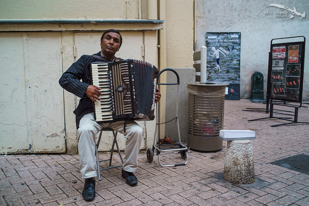 Modern France: South Indian guy plays stereotypical French accordion music in historic square in Antibes