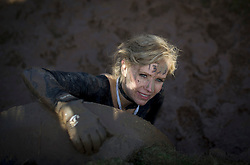 """©  London News Pictures. 27/01/2013.  A female competitor crawling from a tunnel as she ispushed to the limits in the 2013 Tough Guy Challenge on January 27, 2013 in Wolverhampton, England. The event has been widely described as """"the toughest race in the world"""", with over one-third of the starters failing to finish in a typical year. Photo credit: Ben Cawthra"""