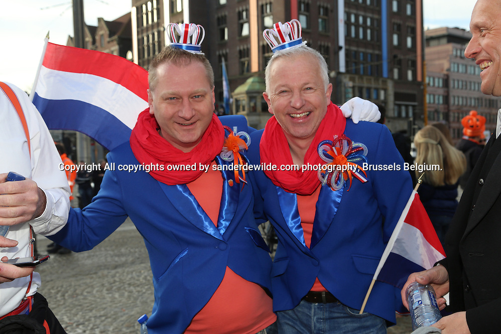 30th April 2013 Amsterdam, Netherlands. Dam Square. Queen Beatrix' abdication takes place, and her son Prince Willem-Alexander will be King of the Netherlands. Two gay men dressed up in the national colors red white blue and orange