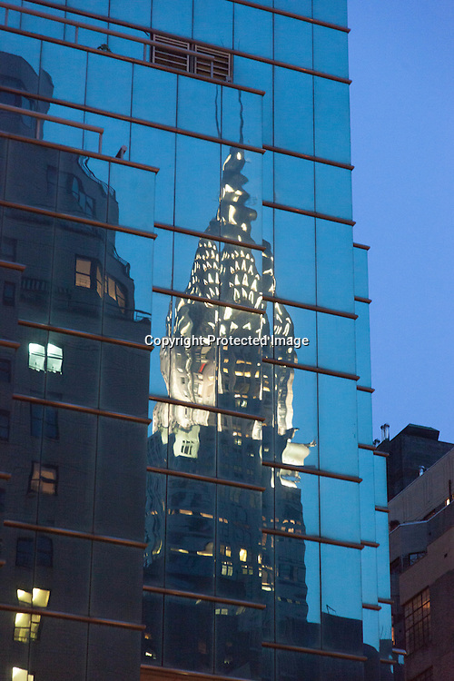 New York ; Chrysler building reflected on a mirror tower at dusk