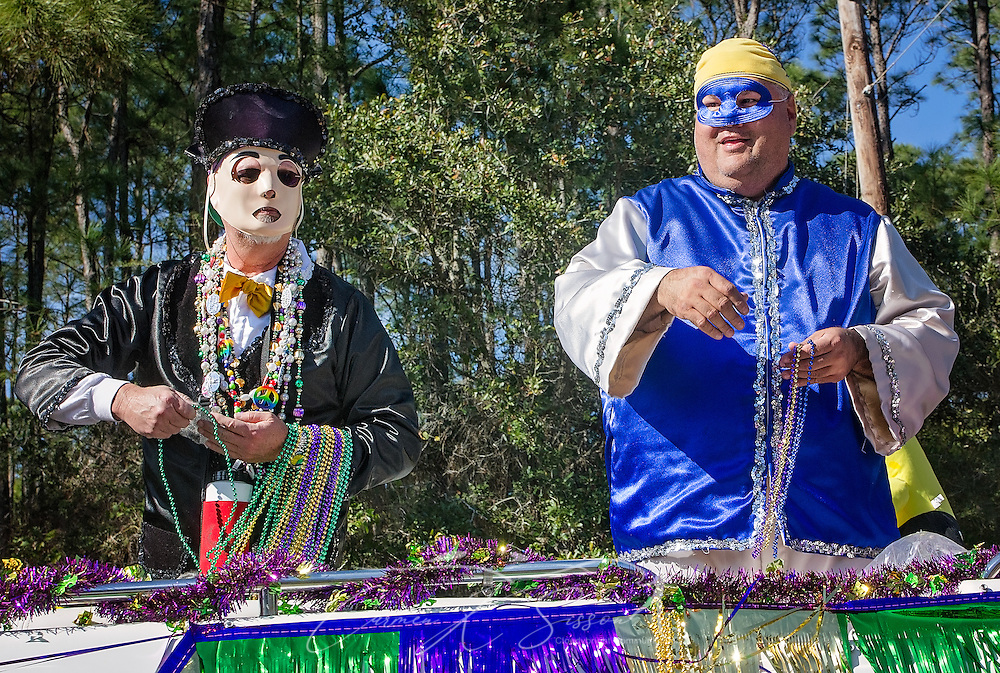 Masked riders throw beads during the first People's Mardi Gras Parade, Feb. 4, 2017, in Dauphin Island, Alabama. French settlers held the first Mardi Gras in 1703, making Mobile's celebration the oldest Mardi Gras in the United States. The first parade of the season is traditionally held on Dauphin Island and draws thousands. (Photo by Carmen K. Sisson/Cloudybright)