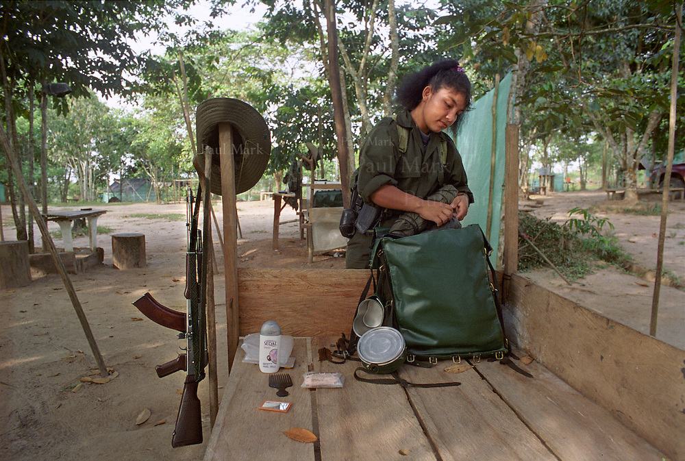 Claudia a young woman guerrilla in a FARC encampment packs her kit next to her AK-47 a few days before the end of the peace talks.