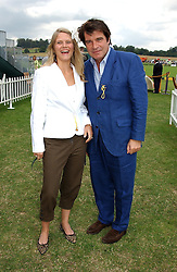 Actoor OLIVER TOBIAS and his wife ARABELLA at the Veuve Clicquot sponsored Gold Cup or the British Open Polo Championship won by The  Azzura polo team who beat The Dubai polo team 17-9 at Cowdray Park, West Sussex on 18th July 2004.
