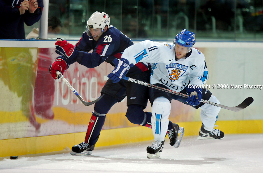 Team U.S.A.'s Erik Cole (#26) tries to sneak past the check of Team Finland's Saku Koivu (#11) during the first period of their Quarterfinal game at the Palasport Olimpico in Turin, Italy on Wednesday February 22, 2006. The winner advances in the tournament and the loser is finished for the 2006 Winter Olympics. The U.S. Hockey Team lost the game 4-3 and was eliminated from the playoffs..(Photo by Marc Piscotty / © 2006)