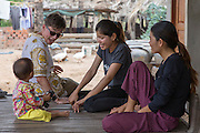 ICS volunteers Dan Hensman & Sokuntheary Nhel entertaining the children and chatting with the family in the host home, in the village of in Banteay Char, near Battambang, Cambodia.