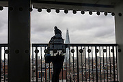 A woman wearing a bobble hat looks out at the London cityscape, on the viewing terrace at Tate Modern art gallery, on 13th January 2017 in London, England.