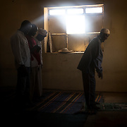 Men are praying in a Mosk. The Nuba are entirely tolerant to religions. Often, people from the muslim religion might marry people from Christian background and vice versa.