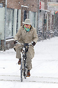 Een man fietst op Oudenoord in Utrecht door de sneeuw. Het fietspad is niet meer zichtbaar.<br /> <br /> A man is cycling in the snow at Oudenoord Utrecht.