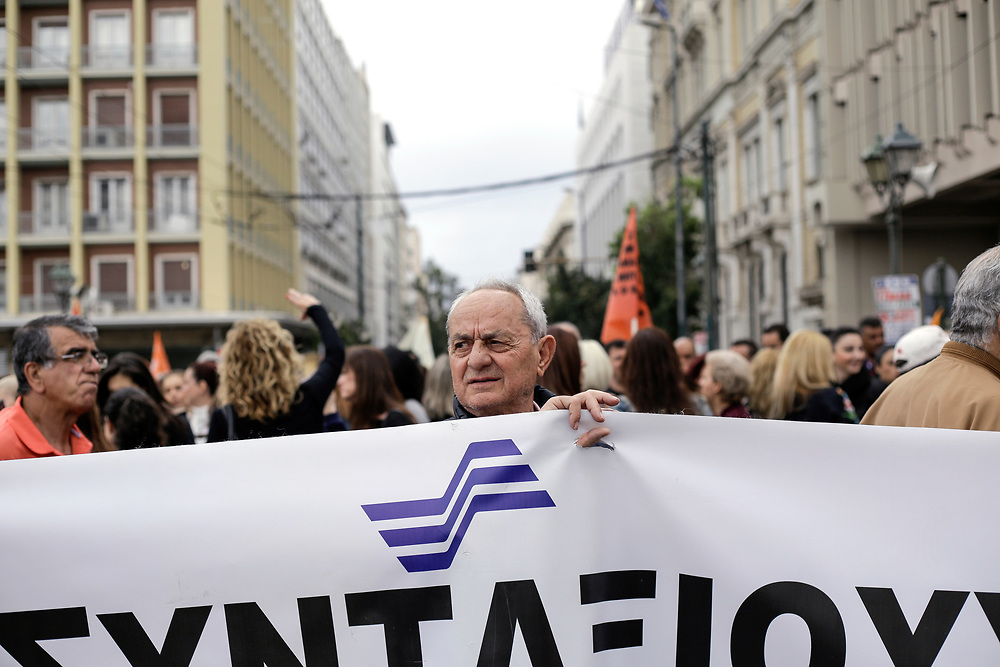 ATHENS, GREECE. May 17, 2017 - A man holds a banner during a 24 hour general strike against further austerity measures to be taken by the Greek Government.