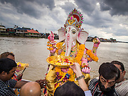 """15 SEPTEMBER 2013 - BANGKOK, THAILAND: Hindus in Bangkok push statues of Ganesha into the Chao Phraya River on the last day of Ganesha Chaturthi celebrations at Shiva Temple in Bangkok. Ganesha Chaturthi is the Hindu festival celebrated on the day of the re-birth of Lord Ganesha, the son of Shiva and Parvati. The festival, also known as Ganeshotsav (""""Festival of Ganesha"""") is observed in the Hindu calendar month of Bhaadrapada. The festival lasts for 10 days, ending on Anant Chaturdashi. Ganesha is a widely worshipped Hindu deity and is revered by many Thai Buddhists. Ganesha is widely revered as the remover of obstacles, the patron of arts and sciences and the deva of intellect and wisdom. The last day of the festival is marked by the immersion of the deity, which symbolizes the cycle of creation and dissolution in nature.  In Bangkok, the deity (statue) was submerged in the Chao Phraya River.         PHOTO BY JACK KURTZ"""