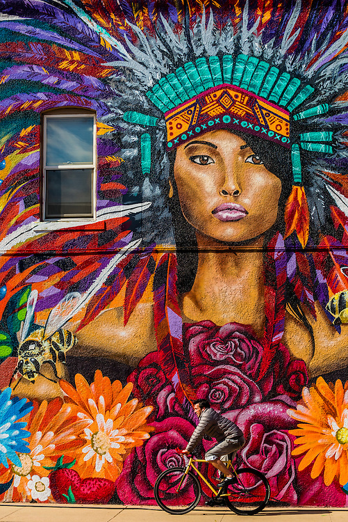 People passing in front of large mural on a building on Downing Street, near Downtown Denver, Colorado USA.
