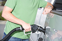 Young man with fuel pump, mid section