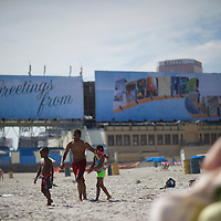 With the famed billboard greeting visitors in the background, a family heads to the ocean on the beach in Atlantic City, NJ on September 3, 2014.  Economically the city is struggling, 4 casinos have already or will be closing in the near future.