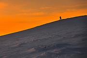 Tourist climbs up a snow mountain hill at sunrise
