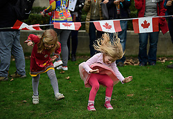 © Licensed to London News Pictures. 20/02/2017. London, UK. Two young Canadian gils play limbo underneath bunting of the Canadian flag during protest held by foreign nationals, living in the UK, outside the Houses of Parliament in London as members of the House of Lords debate the article 50 bill. Photo credit: Ben Cawthra/LNP
