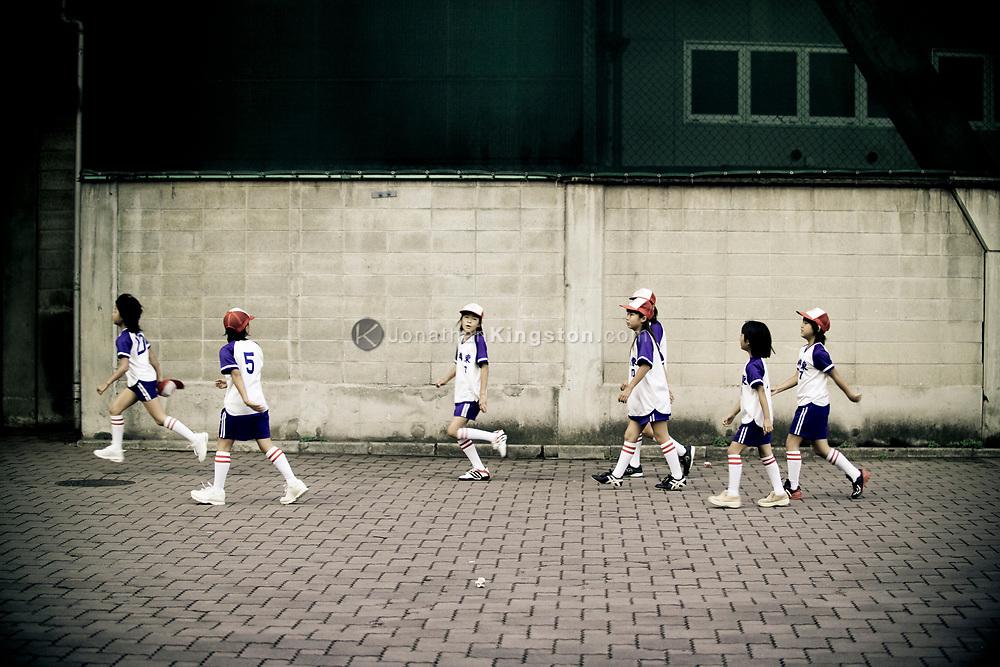 Children run to the baseball stadium in Hiroshima, Japan for a Little League baseball tournament.