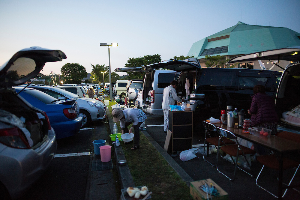 KUMAMOTO, JAPAN - APRIL 19: Residents wash their plates after eating in the carpark of Mashiki Gymnasium evacuation center on April 19, 2016 in Mashiki, Kumamoto, Japan. This is the fourth day in the evacuation center since magnitude-6.3 quake hit Kumamoto city.<br /> <br /> Photo: Richard Atrero de Guzman