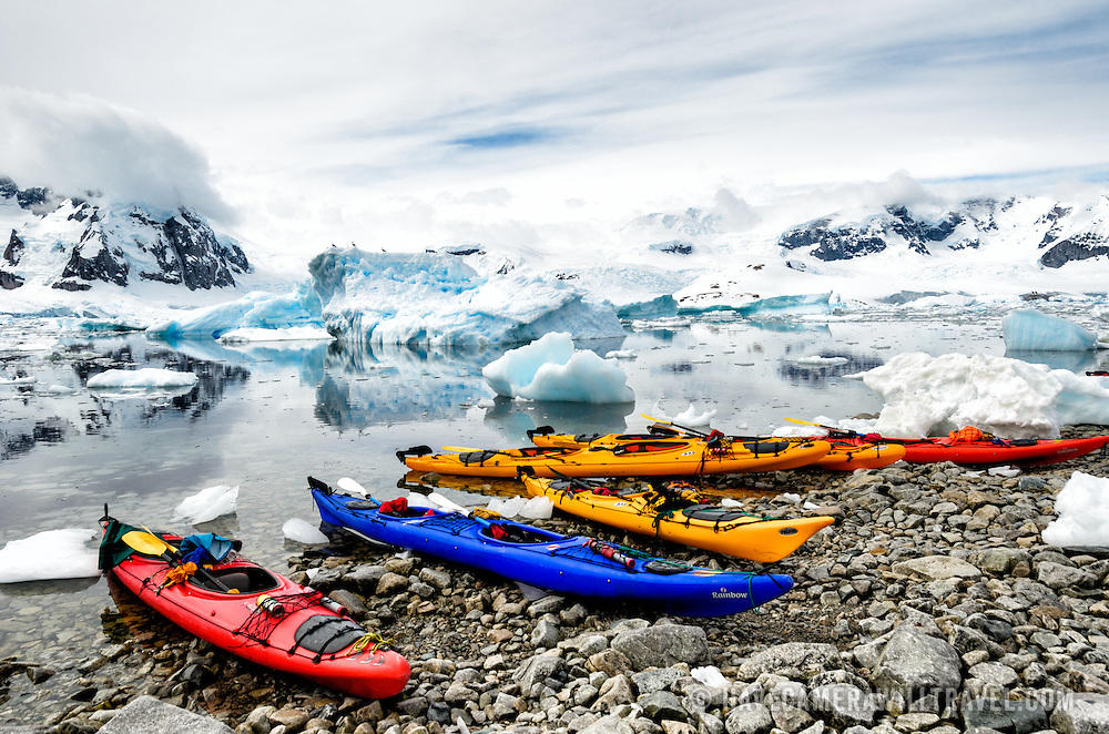 Brightly colored tandem kayaks pulled up on the rocky shore amongst the brash ice and icebergs at Cuverville Island on the Antarctic Peninsula.