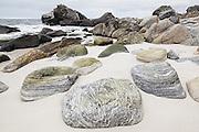 Smooth granite boulders on a sandy beach on Vaeroy Island, Lofoten Islands, Norway.