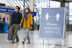 © Licensed to London News Pictures. 05/06/2020. London, UK. A couple wearing face coverings walk past a 'PLEASE KEEP YOUR DISTANCE' sign on Waterloo Station concourse. The government has ordered that commuters will have to wear face coverings on public transport in England from 15 June. Photo credit: Dinendra Haria/LNP