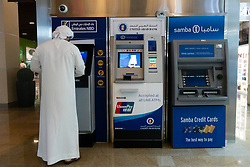 Emirati man using cash ATM machine in Dubai, UAE