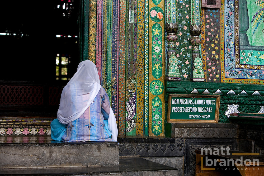A woman kept outside of the Shaw-i-Hamdan Shrine.