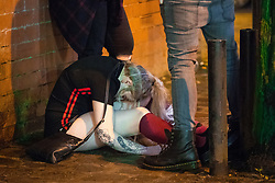 © Licensed to London News Pictures . 01/01/2018. Manchester, UK. A woman sits slumped over on Canal Street , in the Gay Village . Revellers celebrate the start of the New Year in Manchester City Centre . Photo credit: Joel Goodman/LNP