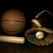 A studio shot of an American Football, a basketball and a baseball ball, mitt and bat. 17th October 2012. Photo Tim Clayton