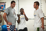 BEAUFORT, SC - JULY 14: Shouting over the clammer of steel weights, CJ Cummings talks about technique with Caleb Gee, left, and Cal Laffite, right, at the weight lifting facility at the Beaufort Middle School on July 14, 2014 in Beaufort, South Carolina. Cummings is competing at the Open Men's Nationals in July.  (Photo by Stephen B. Morton for The Washington Post)
