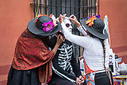 A foreign tourist has skeleton face paint applied by make-up artists during the Dead of the Dead festival in San Miguel de Allende, Mexico. The multi-day festival is to remember friends and family members who have died using calaveras, aztec marigolds, alfeniques, papel picado and the favorite foods and beverages of the departed.