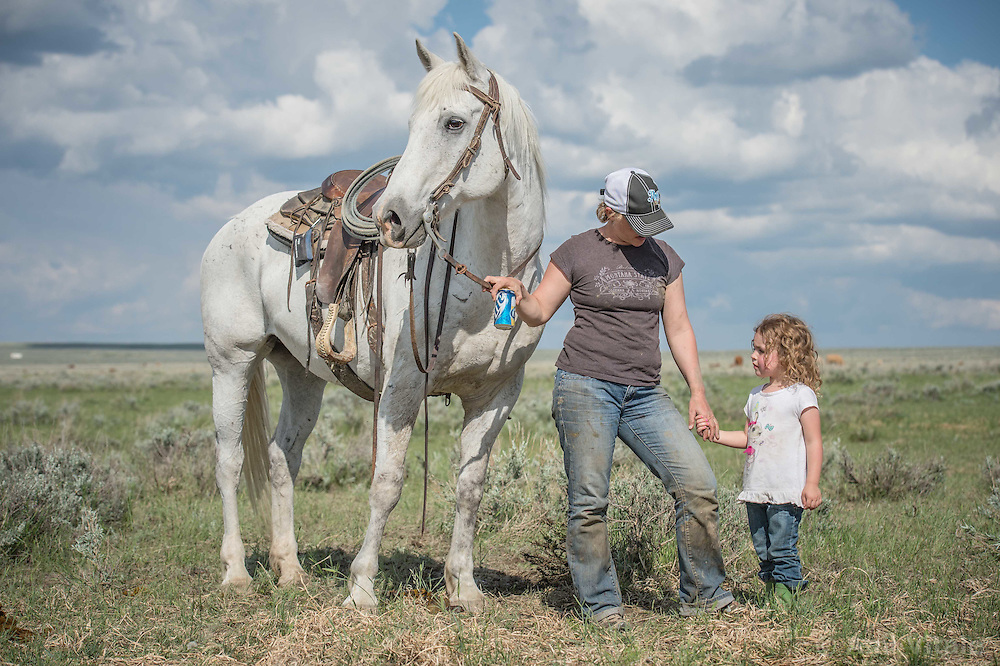 Marian Barthlemess holds Courtney Merrimen's hand on the Barthelmess Ranch near Malta, Montana on June 1, 2013. The Barthelmess Ranch is part of an innovative grass bank project that allows ranchers to graze their cattle at discounted rates on Nature Conservancy land in exchange for improving conservation practices on their own &ldquo;home&rdquo; ranches. In 2002, the <br /> Conservancy began leasing parts of the ranch to neighboring ranchers who were suffering from several years of severe drought essentially offering the Matador&rsquo;s grass to neighboring ranches in exchange for their  participation in conservation efforts. Thirteen ranchers graze their cattle on the Matador and the grassbank has enabled TNC to leverage conservation on more than 225,000 additional acres of private land without the cost of purchase of the land or of easements. (Photo By Ami Vitale)