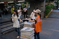 Free newspapers handed out at Central station, Hong Kong.
