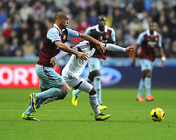 West Ham United's Winston Reid battles for the ball with Swansea City's Jonathan de Guzman - Photo mandatory by-line: Joe Meredith/JMP - Tel: Mobile: 07966 386802 27/10/2013 - SPORT - FOOTBALL - Liberty Stadium - Swansea - Swansea City v West Ham United - Barclays Premier League