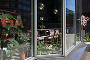 As the UK's Coronavirus death toll during the government's social distancing lockdown, rose by 384 to 33,998, and the R rate of infection is reported to be between 0.7 and 1.0, empty seats are seen through the window of a bar and kitchen on the Euston Road, on 15th May 2020, in London, England.