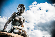 Copenhagen's The Little Mermaid (Den Lille Havfrue) pictured against a blue and cloudy sky