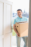 Happy man carrying cardboard box while entering new house