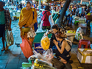 30 JUNE 2016 - BANGKOK, THAILAND:  Flower vendors pray after presenting alms to a Buddhist monk at the sidewalk market in front of Pak Khlong Talat. Sidewalk vendors around Pak Khlong Talat, Bangkok's famous flower market, face eviction if they reopen on July 1. As a part of the military government sponsored initiative to clean up Bangkok, city officials have been trying to shut down the sidewalk vendors around the flower market. The vendors were supposed to be gone by the end of March, but city officials relented at the last minute with a compromise allowing vendors to stay until June 30. When vendors dismantled their booths after business on June 30, they weren't sure if they will be allowed to reopen July 1. Some vendors have moved to new locations approved by the government but many have not because they can't afford the higher rents in the new locations.    PHOTO BY JACK KURTZ