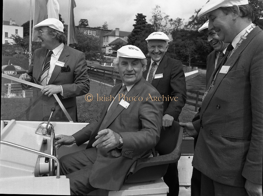 New Facilities At Emerald Star Line.   (R59)..1987..08.06.1987..06.08.1987..8th June 1987..the Minister for Transport and Tourism, Mr John Wilson TD opened a new Customer Service Facility at Emerald Star Line,Carrick on Shannon. Following the viewing of the facility and the planting of a commemorative tree, the Minister, accompanied by Mr Brian Slowey,Managing Director, Guinness,Ireland and Mr E H Bodell, Chairman, Emerald Star line departed on a cruise of The Shannon aboard an Emerald Star Cruiser...Image shows the Minister, John Wilson TD taking command of one of the Emerald Star Cruisers. On board are; Mr P J Ryan,M D,Emerald Star Line,Mr E H Bodell,Chairman Emerald Star Line, Mr Michael McDonnell,Asst Sec,dept of Tourism, Mr Brian Slowey, M D, Guinness Ireland,Deputy John Ellis,Chairman, Leitrim Co Council and Mr Paddy Doyle, County Manager...