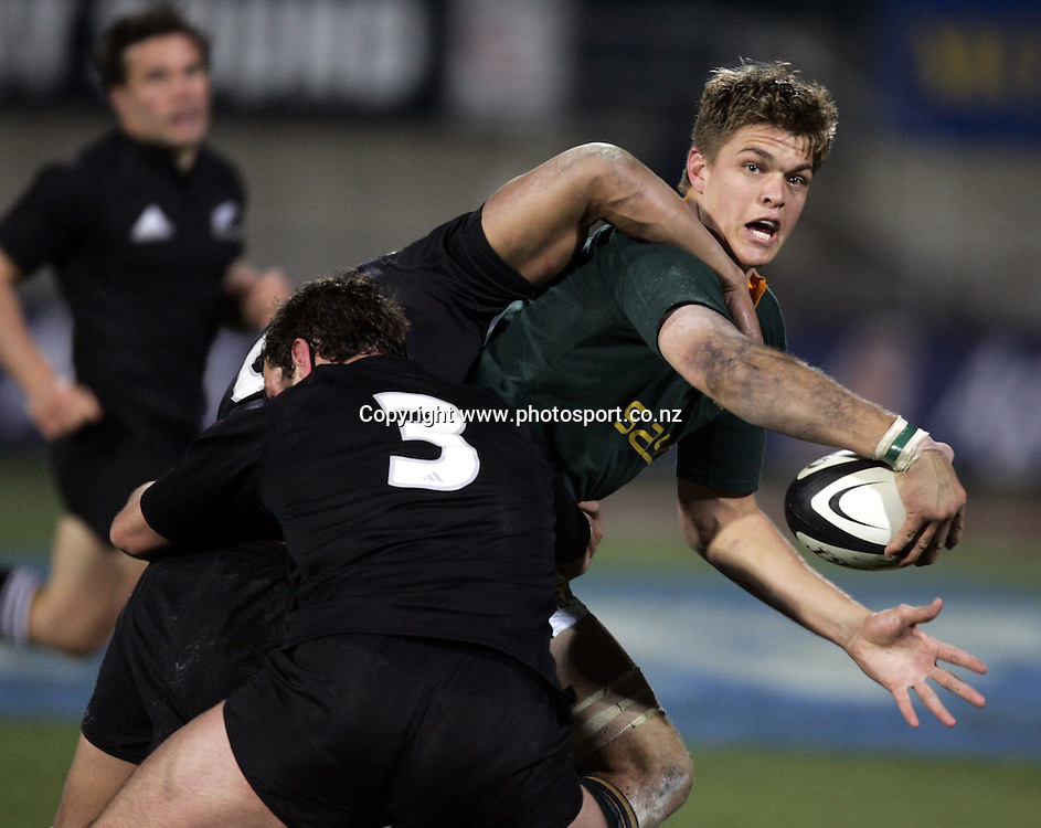 South African flanker Juan Smith is tackled by Tony Woodcock during the Tri Nations rugby test match between the All Blacks and South Africa at Carisbrook in Dunedin, New Zealand on Saturday 27 August, 2005. The All Blacks won 31-27. Photo: Anthony Phelps/PHOTOSPORT<br /><br /><br />132837