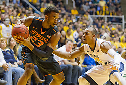 Jan 9, 2016; Morgantown, WV, USA; Oklahoma State Cowboys guard Leyton Hammonds (23) is guarded by West Virginia Mountaineers guard Jevon Carter (2) during the first half at the WVU Coliseum. Mandatory Credit: Ben Queen-USA TODAY Sports