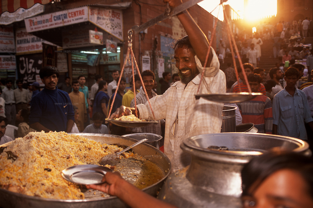 A vendor measuring the weight of the rice seving on the plate as a young boy reaches another empty plate to be loaded as the sun sets behind him at a biryani stall near the Jama Masjid, New Delhi.