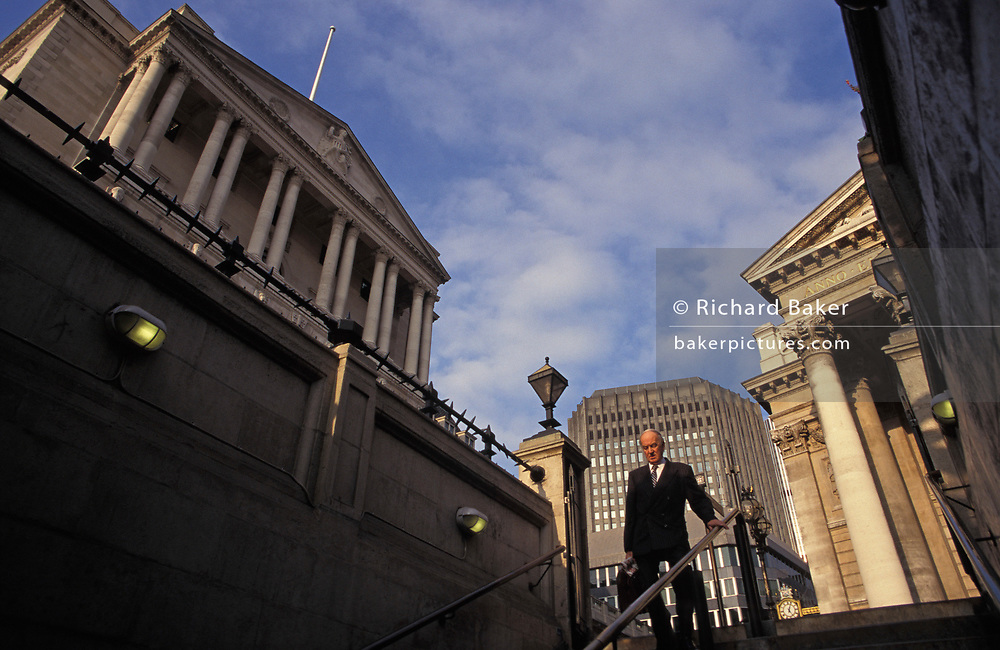 Beneath the columns of the Bank of England (left) and Cornhill Exchange (right) an older City gentleman descends the steps into Bank underground station, on 20th April 1994, in London, England.