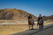 Horse riders along the highway cutting through Golok region, TIbet (Qinghai, China).