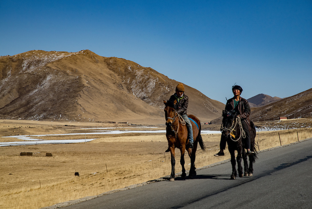 Horse riders along the highway cutting through Golok region, TIbet (Qinghai, China).
