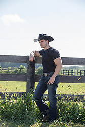 manly good looking cowboy by a split rail fence