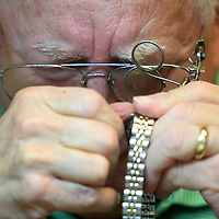Thomas Scott, owner of Scott's Watch and Jewelry in Tupelo, looks through one of his magnifiers attached to his reading glasses as he replaces the movement into a customers Fossil watch. Scott has been repairing watches since he was 15 years old. Now at 65, he has been working for himself in Tupelo the last 25 years.